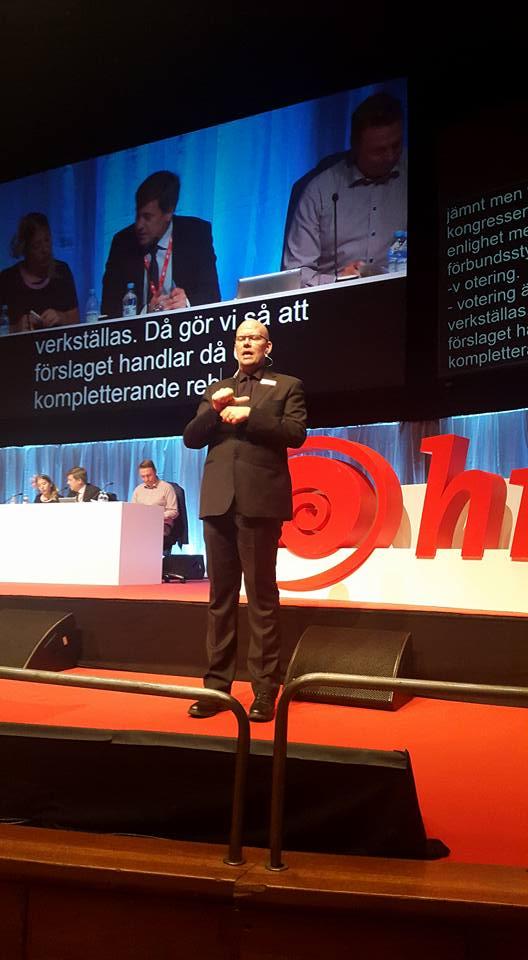 Tolken Jonas Seger med svart kostym, svart skjorta och svart slips tolkar under HRF:s kongress. Han har tolkskylt på sitt vänstra kavajslag och tecknar precis siffran sexton. Bakom honom ser man en väldigt stor skärm med skrivtolkning och på skärmen visas även storbild av presidiet som sitter på scenen bakom Jonas. Man kan också se en del av HRF:s stora logga bakom Jonas.