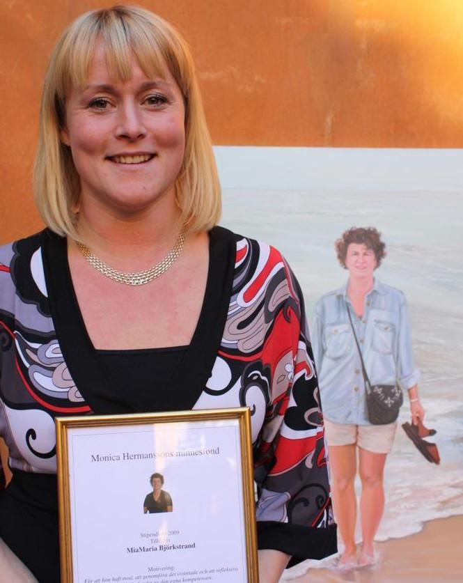 Foto på MiaMaria Björkstrand när hon precis mottagit Monica Hermanssons stipendium vid en ceremoni. Hon har blont axellångt hår med lugg, dagen till ära en stormönstrad klänning och i händerna håller hon sitt diplom som är inramat med guldram. Bakom Maria finns en stor oljemålning av Monica Hermansson när hon går barfota i strandbrynet med beiga shorts och ljus jeansskjorta, diagonalt över bröstet hänger en svart handväska och i handen håller hon sina sandaler.