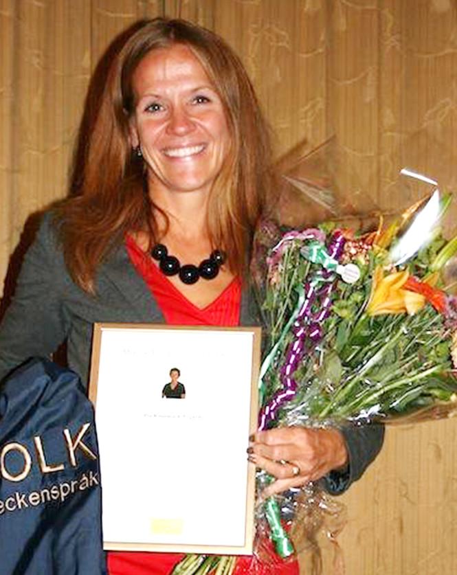 Foto på Pia Rönnmark Nygårds när hon fått motta Monica Hermanssons stipendium under en ceremoni. Hon har långt brunt utsläppt hår, röd klänning med grå kavaj, ett halsband med svarta stora kulor. Hon ser väldigt glad ut och håller i en stor blombukett inslagen i cellofan, sitt diplom inramat i guldram samt en kostymväst som det står TOLK Teckenspråk broderat på ryggen.