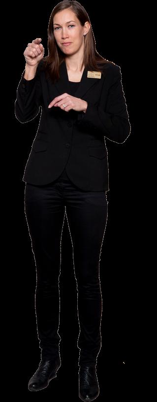 Tolken Sofia Lindfors i helfigur. Hon har långt brunt utsläppt hår, svart kavaj med en tolkskylt på vänster sida, svarta byxor och skor. Hon säger något på teckenspråk och pekar mot dig.