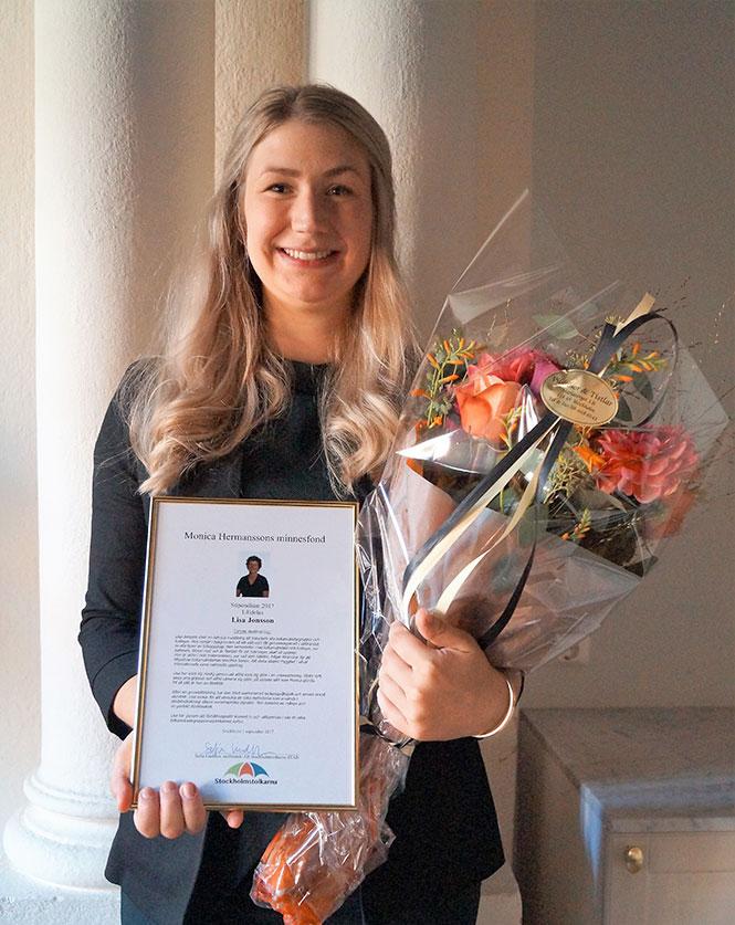 Blonda Lisa Jonsson poserar leendes med ett Monica Hermanssons diplom och en bukett med röda, orange och gröna blommor inslagna i cellofan i famnen.